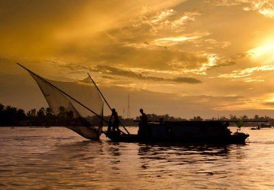 Fischerboot im Sonnenuntergang auf dem Mekong - Vietnam
